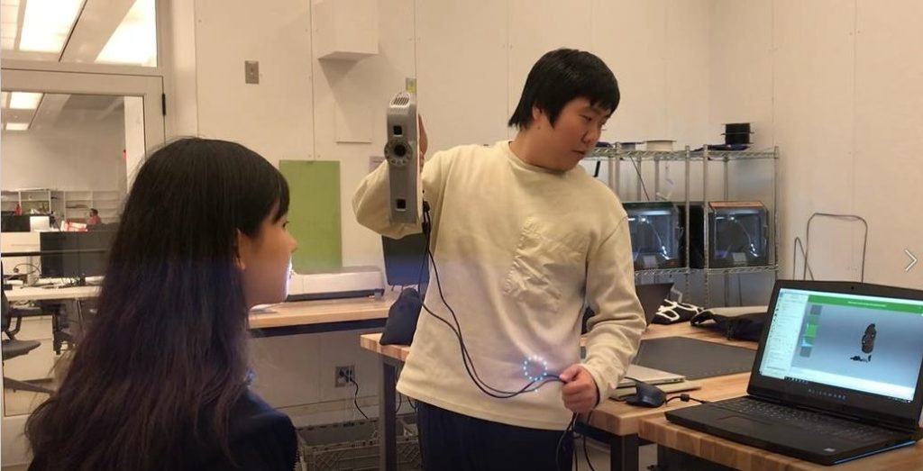 Photo of Joon, 3D Scanning TA, using hand-held scanner to capture bust of another individual. Work Room 224 of Sackler, 485 Broadway.